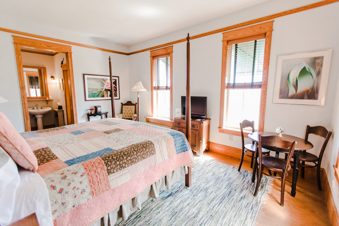Downstairs Room 1 King Bed Facing Windows and Bathroom Entrance